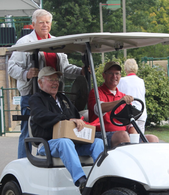 men sitting in golf cart smilingwith a man holding on the back of cart