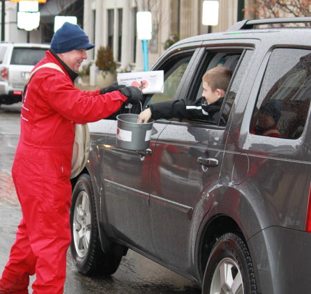 man handing paper to small boy in a car